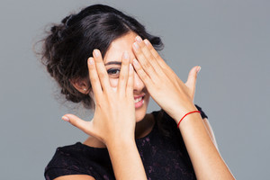 Happy woman covering her eye with finger