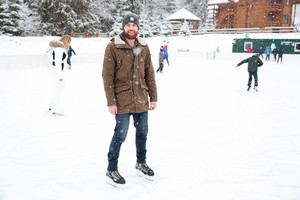 Smiling man ice skating outdoors