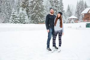 Couple in ice skates hugging and looking at camera outdoors