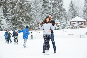 Smiling couple in ice skates hugging outdoors