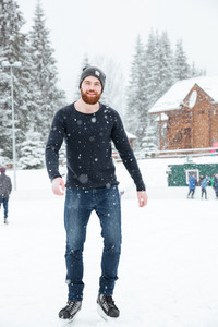 Handsome man ice skating outdoors