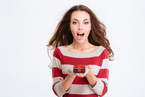 Cheerful amazed woman holding gift box