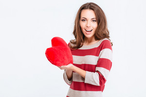 Portrait of a cheerful woman holding red heart