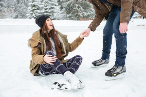 Man helping girl to stand on the ice rink