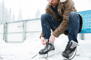 Man tying shoelace on ice skates outdoors