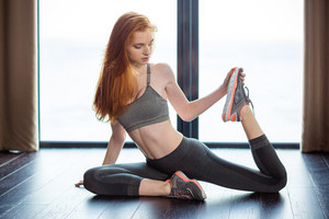Redhair woman stretching legs