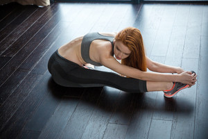 Fitness redhead woman stretching legs