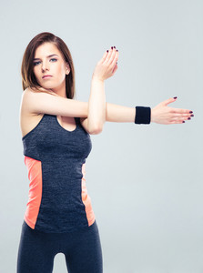 Young fitness woman stretching hands