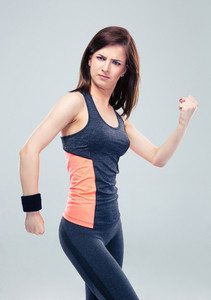 Fitness woman posing on gray background