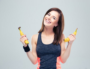 Happy sporty woman holding bananas