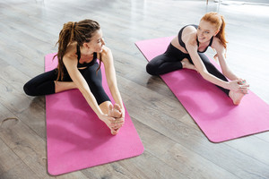 Two young women sitting and stretching in yoga center