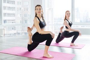 Two beautiful women stretching legs in yoga center