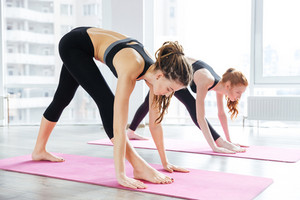 Two women doing exercises in yoga center