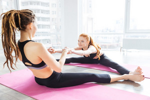 Two smiling women stretching together in yoga center