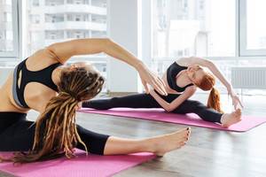 Two women doing exercises and stretching in yoga studio