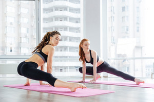 Two women stretching legs together in yoga studio