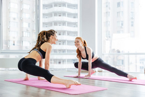 Two happy women doing stretching exercises together in yoga studio