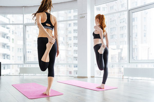 Two women standing and stretching legs on pink yoga mat