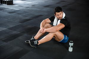 Sportsman sitting on the floor in gym
