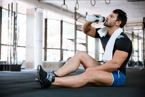 Fitness man sitting on the floor and drinking water