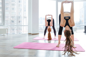 Two women practicing yoga in studio