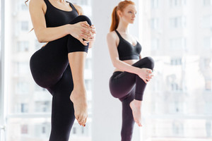 Closeup of two attractive young women standing and stretching legs