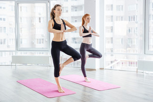 Two beautiful young women practicing yoga
