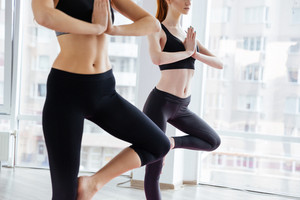Two women standing and doing balancing pose in yoga studio
