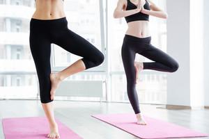 Two women doing balancing pose on pink yoga mat