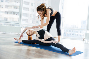 Woman doing twin and stretching legs with her coach