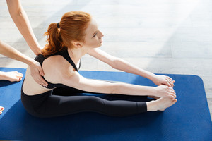 Lovely redhead young woman doing yoga with personal trainer