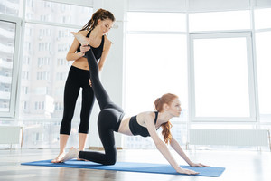 Beautiful woman doing exercises on mat with personal trainer