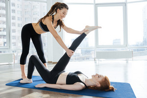 Happy woman stretching legs with personal trainer