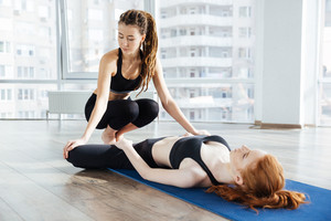 Trainer stretching legs of woman lying on the floor