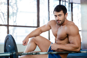 Male bodybuilder resting in fitness gym