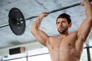 Man workout with barbell in fitness gm
