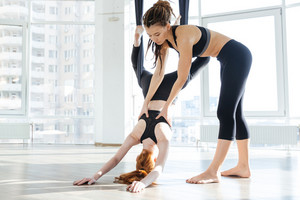 Pretty redhead girl practicing aerial yoga with personal trainer