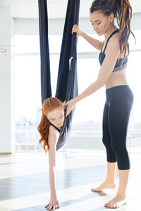 Trainer teaching woman doing aerial yoga using hammock