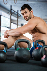Muscular man sitting in fitness gym with kettle balls