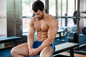 Man sitting on the bench at fitness gym