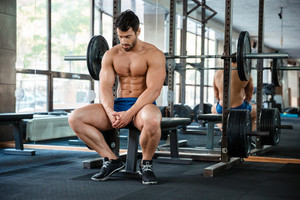 Man resting on the bench in fitness gym