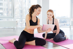 Two happy  women using tablet sitting in yoga studio