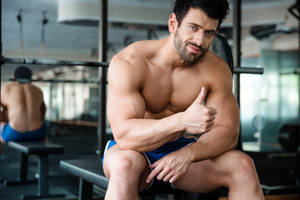 Muscular man sitting on the bench and showing thumb up