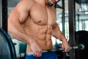 Male chest with barbell in gym
