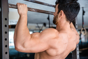 Man tightening on horizontal bar at gym