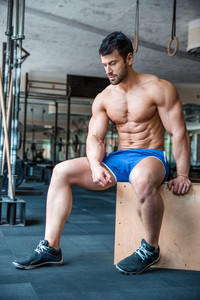 Muscular man resting in fitness ym