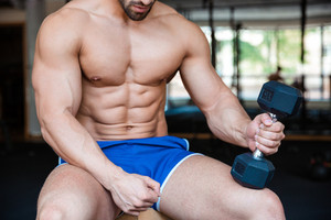 Muscular man workout with dumbbell
