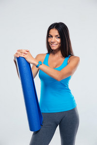 Happy sports woman holding yoga mat