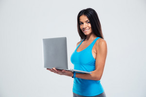 Happy fitness woman using laptop