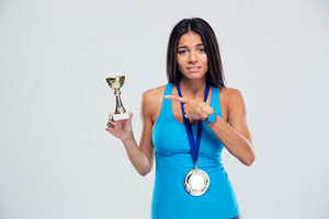 Sports woman pointing finger on the winners cup